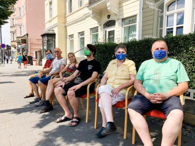 Das LAG-Team zieht um - sitzen auf roten Stühlen am Schlesischen Platz in Dresden